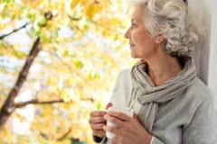 grauhaarige, attraktive Frau geniet den sonnigen Herbst